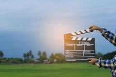 Lura att spela filmclapperbrädet mot sommarhimmelbakgrund Begrepp för filmdirektör Arkivfoton