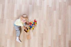 Lura att spela med färgrika leksaker på bästa sikt för golv Arkivbilder