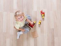 Lura att spela med leksaker på bästa sikt för golv Royaltyfri Bild