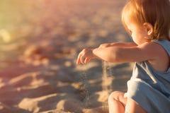 Lura att spela med sand på stranden vid havet royaltyfria bilder