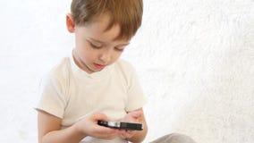 Lura att spela med smartphonen på vit bakgrund och att le Närbild arkivfilmer