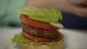 Lura att stapla hamburgareingredienser som förbereder sig att äta skräpmat, fetmaproblem arkivfilmer