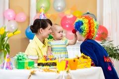 Behandla som ett barn den fira första födelsedagen för flickan med föräldrar och clownen Arkivfoton
