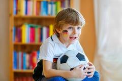 Lura den hållande ögonen på fotboll- eller fotbollleken för pojke på tv Royaltyfri Fotografi