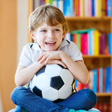 Lura den hållande ögonen på fotboll- eller fotbollleken för pojke på tv Arkivbild