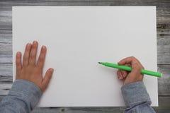 Lura den hållande pennan på det tomma arket av papper Arkivbild