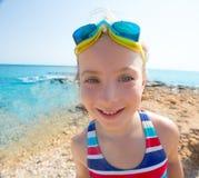 Lura för vinkelstrand för rolig flicka den breda baddräkten och skyddsglasögon för stående Royaltyfria Foton