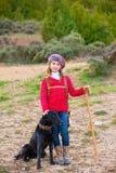 Lura flickaherdinnan som är lycklig med hunden och flocken av får Royaltyfri Fotografi