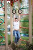 Lura flickan som hänger på cirklarna på ungelekplats fotografering för bildbyråer