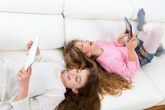 Lura flickor som har gyckel som spelar med den liggande soffan för minnestavlaPC:n royaltyfri bild