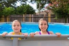 Lura flickor som simmar i pölen i trädgård Arkivfoton