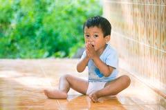 Lura leenden och sitt på golvet Fotografering för Bildbyråer