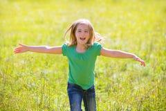 Lura lyckliga rinnande öppna händer för flickan i grönt utomhus- Arkivfoton