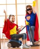 Lura och fostra klätt som superheroes som använder dammsugare i rum Familj - kvinna- och ungedottern har en gyckel medan arkivbilder