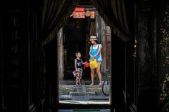 Lura och hans prata för mamma som är bort, medan besöka den hoien, Quang Nam Province, Vietnam royaltyfria bilder