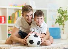 Lura pojken och fadern som spelar med inomhus soccerball Fotografering för Bildbyråer
