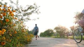 lura pojken och flickan i likformig som går och rider cykeln till skolan i morgon stock video