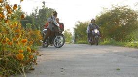 lura pojken och flickan i likformig som går och rider cykeln till skolan i morgon arkivfilmer