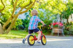 Lura pojken som kör trehjulingen eller cykeln i trädgård Royaltyfri Fotografi