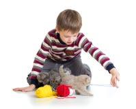 Lura pojken som leker med kattungar på vitbakgrund Arkivbilder