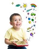 Lura pojken som rymmer en minnestavlaPC i händer och ser upp fotografering för bildbyråer
