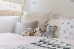 Lura rum med dockor och kuddar på säng Arkivfoton