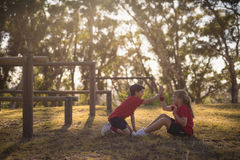 Lurar att ge höjdpunkt fem till varandra, medan öva under hinderkurs fotografering för bildbyråer