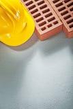 Lurar den hårda hatten för byggnadstegelstenar på konkret bakgrundskonstruktion Arkivfoton