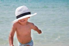 Lurar den utomhus- livsstilen Lycklig gullig pojke i Panama som spelar med sand på stranden av havet Sommarsemester och familj arkivfoto