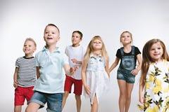 Lurar det gulliga förskolebarnet för gruppmode vänner som tillsammans poserar och ser vit bakgrund för kameran arkivfoton