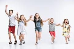 Lurar det gulliga förskolebarnet för gruppmode vänner som tillsammans poserar och ser vit bakgrund för kameran arkivbild