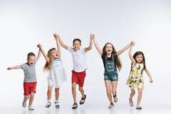 Lurar det gulliga förskolebarnet för gruppmode vänner som tillsammans poserar och ser vit bakgrund för kameran royaltyfri foto