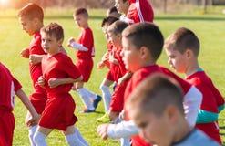 Lurar fotbollfotboll - barnspelare som övar för match Arkivfoto
