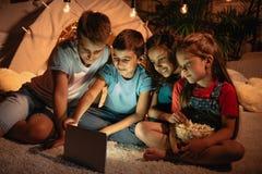 Lurar genom att använda den digitala minnestavlan, medan spendera tid tillsammans hemma arkivbilder