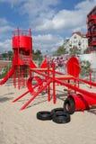 Lurar lekplatsen med den röda glidbanan, klättraren, sandlåda Arkivfoto