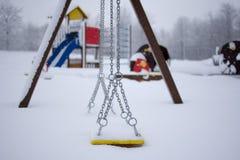 Lurar lekplatsen som täckas med snö Arkivfoto