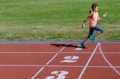 Lurar sporten, barnspring på stadionspår, utbildning och kondition Royaltyfria Bilder