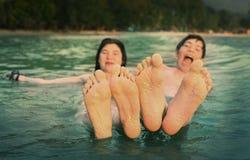 Lurar tonåringfot tätt upp fotoet i havet på den tropiska stranden royaltyfria bilder