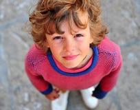 Lurvig pojke i den rosa ärmlös tröja som ser kameran Fotografering för Bildbyråer