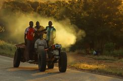 A group of young African black men ride a small tractor on a dirt road, picking up dust at sunset stock photo