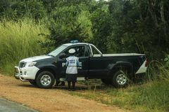 A police car and a black police officer stand on a rural road stock images