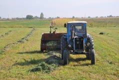 LUSARAT, ARMENIA - 12 DE OCTUBRE DE 2016: Tractor en el heno del campo imagenes de archivo