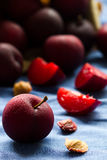 Luscious fresh Black Diamond plums grown in Portugal. Spilled from a paper bag onto blue cloth background. Stock Images