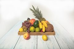 Luscious, gorgeously arranged fruit tray on the table. Healthy fruit background ; Studio photo of different fruits on white and  blue  vintage wooden table Stock Image