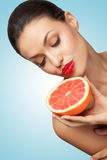 Luscious passion. A creative portrait of a beautiful girl holding a red grapefruit sexually under her chin Royalty Free Stock Images
