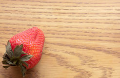 Luscious Red Strawberry. One red strawberry in the corner sitting on wood Royalty Free Stock Photos