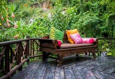 Lush Backyard Patio. Patio furniture with multi colored pillows on dark hardwood deck and beautiful lush foliage garden Stock Images