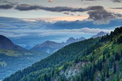 Green pine forests in twilight Carnic and Gailtal Alps Austria. Lush dark green pine forests of Karnische Alpen and gray blue cloud stripes in calm twilight Stock Photography