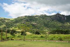 Lush Fiji. Mountain landscape with lush, tropical, and green rainforest under a blue sky with clouds in Port Denarau, Fiji Royalty Free Stock Image