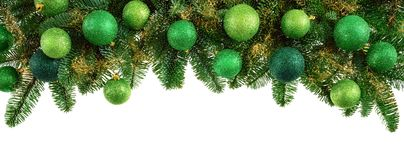 Lush fir twigs and green baubles on white Royalty Free Stock Image